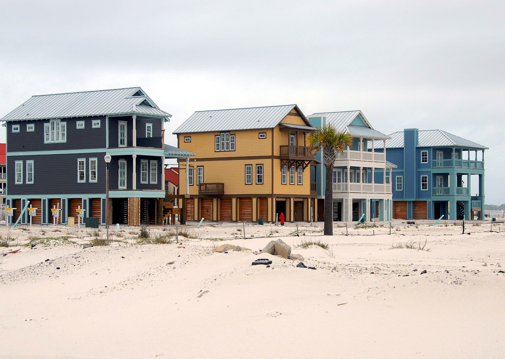 4 houses on the beach with sand and dunes representing why not to invest an IRA in real estate