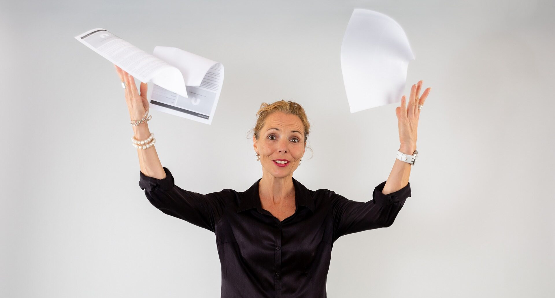 Woman In Black Throwing Papers In The Air Frustrated Needing Help On Pro Tax & Accounting For Bookkeeping
